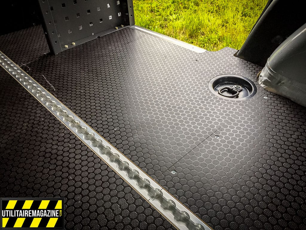 Deux rails aéro courent sur toute la longueur et permettent de fixer des matériaux, des caisses avec des pions d'ancrage. Notez le sol avec un revêtement antidérapant.